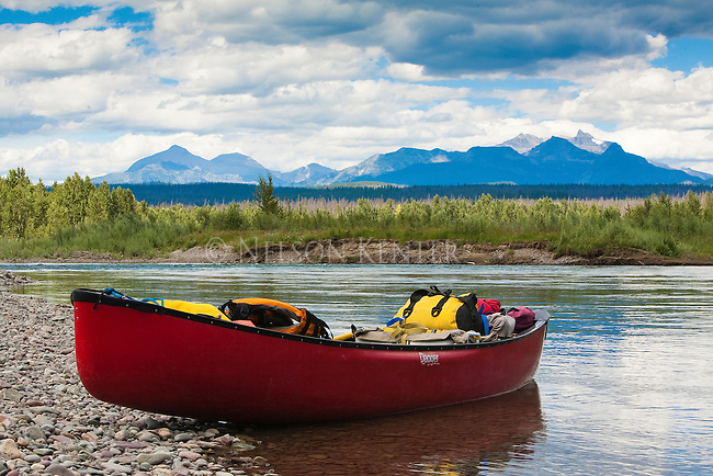 A red canoe on the shore of the North Fork of the Flathead River in Montana with a view of mountains in Glacier National Park