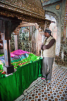 Fatehpur Sikri, Uttar Pradesh, India.  Inside the Mausoleum of Sheikh Salim Chishti a Caretaker Stands beside the Tomb.
