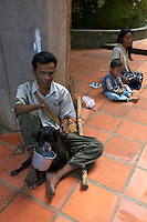 Mans best friend the dog collecting some donation for a mine victim from the Siam reap Area, he lost his hand and eyesight due to an exploding land mine, the left overs from the war CAMBODIA 2007, PHNOM KOLEN The land mine victims of Cambodia