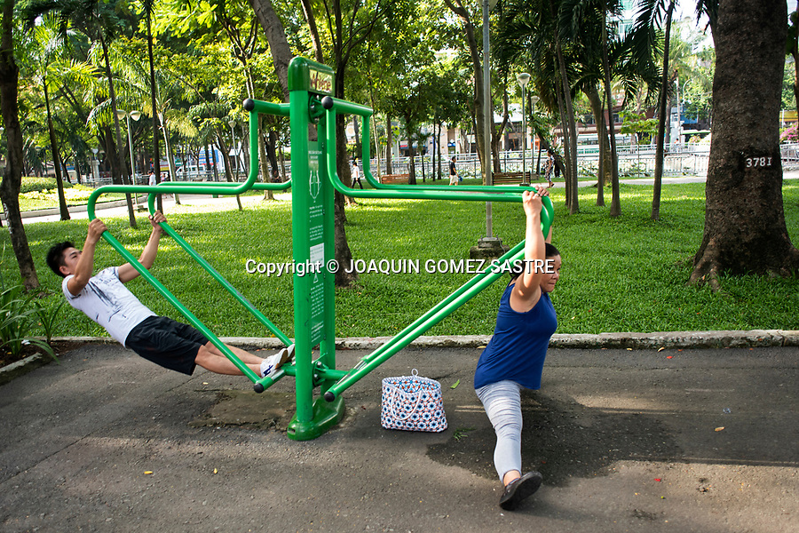 Two people exercise early in the morning in a park in Ho Chi Minh (Vietnam) is very popular vesta custom among the Vietnamese<br /> HO CHI MINH- VIETNAM