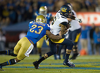 Chris Harper of California runs the ball away from Anthony Jefferson of UCLA during the game at Rose Bowl in Pasadena, California on October 12th, 2013.   UCLA defeated California, 37-10.