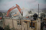 An Israeli worker uses a bulldozer to demolish a Palestinian house in the the Beit Hanina neighborhood of East Jerusalem, January 27, 2014. Israeli authorities on Monday demolished four Palestinian homes in annexed east Jerusalem under the pretext building without construction permits, police and residents said. Photo by Saeed Qaq