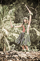Young hula dancer in ti leaf skirt at Hawaiian heiau (temple site) using puili (bamboo slit sticks) wearing maile leaf lei