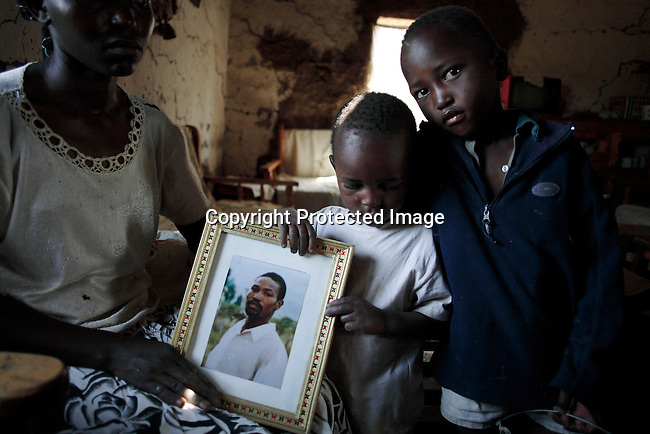 Jack Githuka, age 3, holds the portrait of his late father Robert Njoya as he stands next to his mother Serah older brother Gidrass Mbongoa, age 9, in their house. Photo: Per-Anders Pettersson/Getty Images