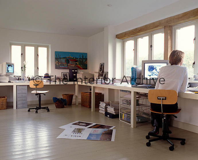 A spacious home office is surrounded by windows