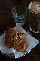 An almond croissant and a glass of cafe latte at cafe at breakfast time.