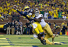 Sept. 7, 2013; Michigan Wolverines quarterback Devin Gardner (98) throws while being tackled by Notre Dame Fighting Irish linebacker Prince Shembo (55) and safety Austin Collinsworth (28) in the fourth quarter.<br /> <br /> Photo by Matt Cashore