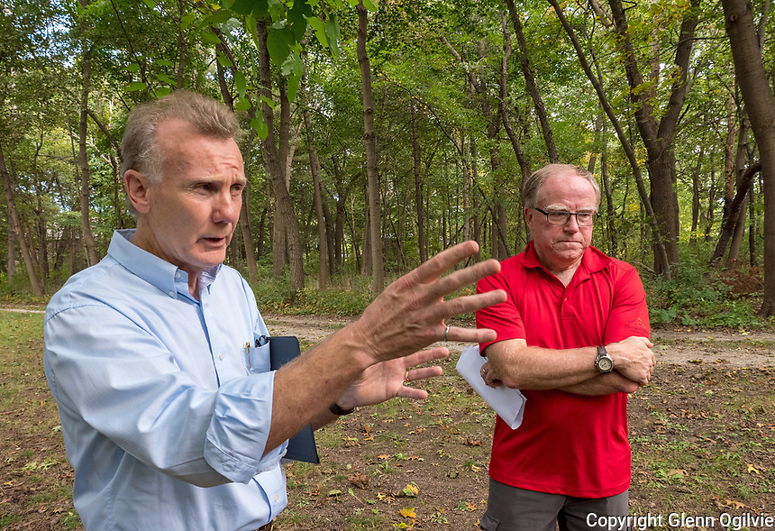 Peter Lynch, blue shirt and Fraser Godfrey stand by a rare urban woodland being threatened by residential development.