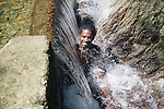 Young man in the waterfall at Top River Falls, Tobago