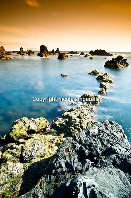 Seascape view from the volcanic coast of Flores Island at the Azores. Tobacco sky