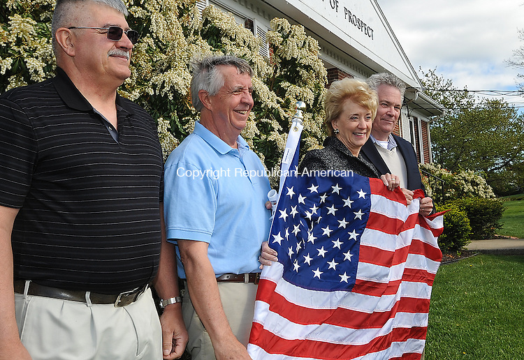PROSPECT, CT-27 APRIL 2012--042712JS01-Linda McMahon, Republican nominee for the U.S. Senate, third from left, poses with Prospect residents Bob Moraniec, left,  Robert A. Hiscox, and Mayor Robert Chatfield outside Prospect Town Hall on Friday as she delivers an American flag to be part of the Prospect Flag Fund started by Hiscox. The group has raised more than $10,000 and purchased 150 American flags to install on utility poles up and down Routes 68 and 69 in the center of town.  Ed Brasche, owner and operator of Ed the Tree Man, will donate vehicles and man power to install the flags and brackets. . Jim Shannon Republican-American