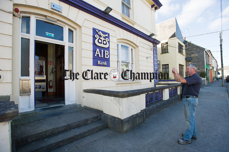 Local man Pat Custy taking a photograph of the AIB bank in Kildysart to mark its closure. Photograph by John Kelly.
