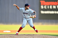 Lakewood BlueClaws starting pitcher Victor Santos (12) attempts a pickoff during a game against the Asheville Tourists at McCormick Field on August 5, 2019 in Asheville, North Carolina. The BlueClaws defeated the Tourists 4-2. (Tony Farlow/Four Seam Images)