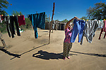 A Wichi indigenous woman hangs her laundry in Lote 75, an indigenous neighborhood of Embarcacion, Argentina. The Wichi in this area, largely traditional hunters and gatherers, have struggled for decades to recover land that has been systematically stolen from them by cattleraisers and large agricultural plantations.