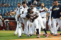 Nashville Sounds pitcher Donovan Hand (48) and second baseman Eugenio Velez (4) celebrate with catcher Matt Pagnozzi (10) after hitting a walk off home run during the first game of a double header against the Omaha Storm Chasers on May 21, 2014 at Herschel Greer Stadium in Nashville, Tennessee.  Nashville defeated Omaha 5-4.  (Mike Janes/Four Seam Images)