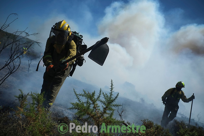 A firefighter from the BRIF (Forest Fire Backup Brigade) looks on as he works at the site of a wildfire in Cualedro, near Ourense on August 24, 2013. (c) Pedro ARMESTRE.