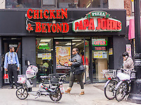 Papa John's Pizza shares space with a Chicken & Beyond in Downtown Brooklyn in New York on Friday, May 2, 2014.  (© Richard B. Levine)