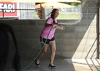 NWA Democrat-Gazette/ANDY SHUPE<br /> Jessika Calhoon, 16, of Farmington laughs Thursday, Sept. 3, 2015, as she uses a water hose to spray friends during the Washington County Fair at the county fairgrounds in Fayetteville.