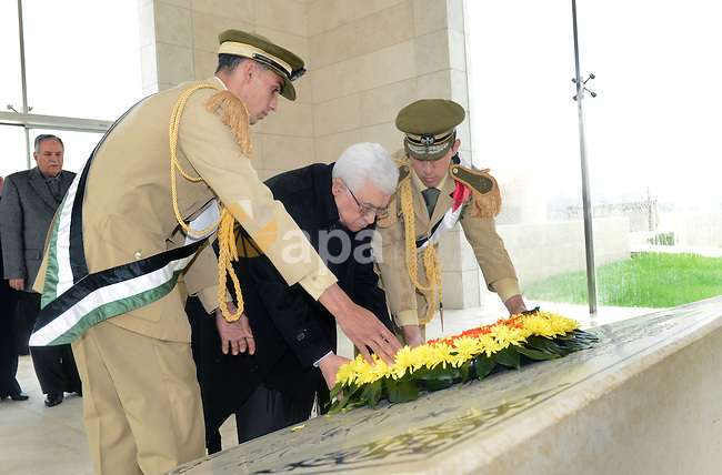 Palestinian President Mahmoud Abbas (C) gives respect after he lays a wreath over late leader Yasser Arafat grave prior the official ceremony of marking Arafat's 8th Anniversary of his death, in the West Bank city of Ramallah on Nov. 11, 2012. Photo by Thaer Ganaim