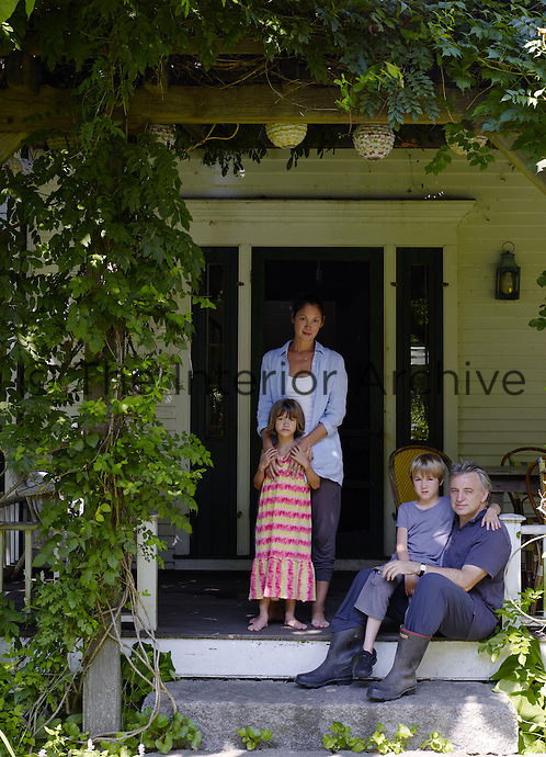 Keith and Alina McNally with their children Alice and George on the porch of their farmhouse