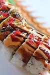 Artistic closeup of red dragon maki sushi roll with salmon and caviar