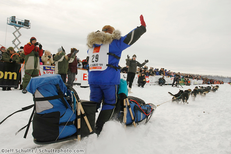 Karin Hendrickson waves to the crowd as she leaves the start line on Sunday during the restart day of Iditarod 2009 in Willow , Alaska