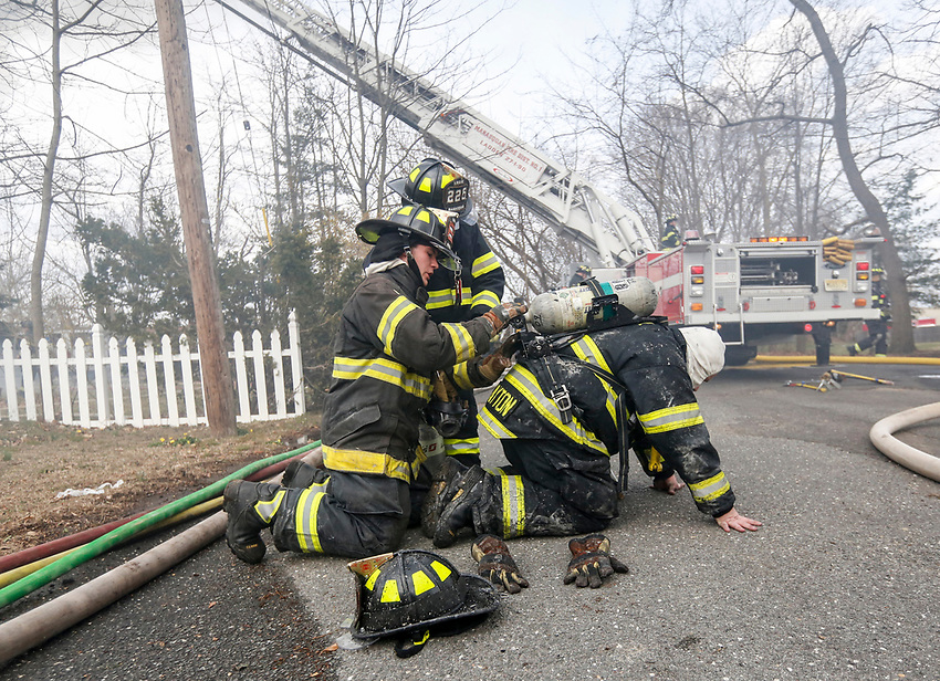 Manasquan firegfighters switch out a SCBA tank for firefighter John Clayton as they work at a structure fire on Easter Sunday, April 1, 2018.