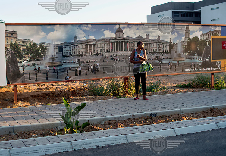 A woman stands beside a billboard displaying a panoramic image of Trafalgar Square in London.