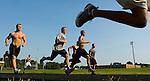 High school football players run sprints during practice in the preseason.