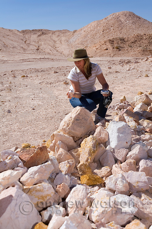 A woman noodles (fossicks) for opals in the dug earth - Coober Pedy, South Australia, AUSTRALIA.