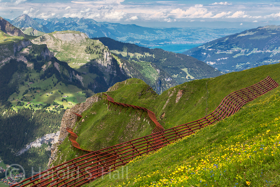 After taking a tram from the hamlet of Murren, Switzerland, one is treated to views of Interlaken and beyond.  The extreme steepness of the mountain slopes requires an array of snow fences to lessen the danger of avalanches in the winter.