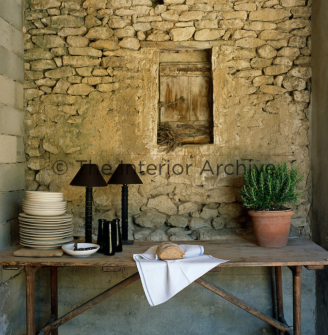 A rustic wooden trestle table with a stack of Provencal creamware against a stone wall