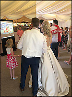 BNPS.co.uk (01202 558833)Pic: LouiseNightingale/BNPS<br /> <br /> The newlywed couple watch the second half together.<br /> <br /> Match of the day...<br /> <br /> A newlywed couple kept football fans at their wedding happy by showing England's game while they had their wedding breakfast.<br /> <br /> Just married Louise Nightingale and Tony Oram organised a big projector and screen in their wedding marquee to show the quarter final as they sat down for the formal dinner.<br /> <br /> Initially their 75 guests politely craned their necks to watch the action unfold from their seats but as things heated up everyone crowded round the screen to see England romp to victory.<br /> <br /> The couple said they were inundated ahead of the game with requests from friends and family to find a way of making the game available at their reception.
