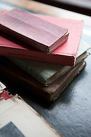 A small stack of books on the desk in the library, dented and faded from years of use