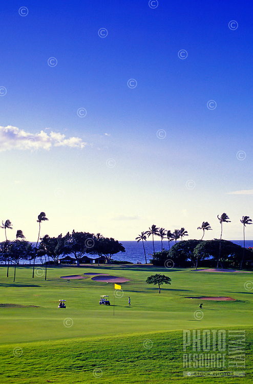 The beautiful greens at the Royal Kaanapali Golf course on Maui with palm trees and the Pacific Ocean in the background.