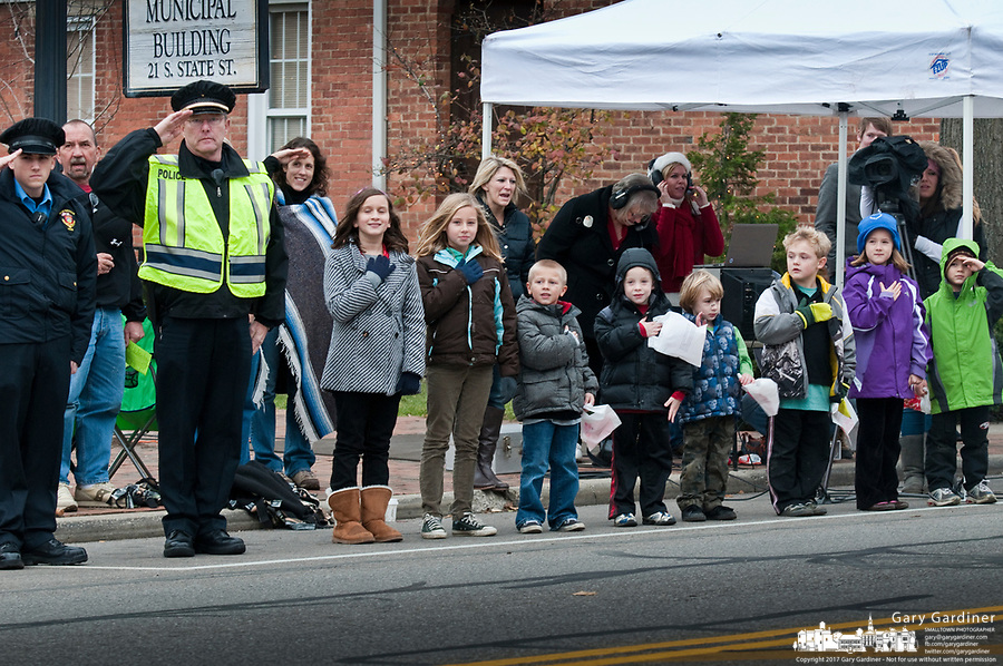 Reserve Police officer Ted Brettaur, with vest at left, leads his charges in saluting the American flag at the front of the city Christmas parade.Westerville Christmas parade.