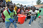 People unload buckets of food and other emergency supplies before distributing them in the Santa Teresa camp in Petionville, Haiti. Hundreds of families left homeless by the devastating January 12 earthquake live here. The ACT Alliance sponsored this February 1 distribution of food, buckets, and hygiene kits.
