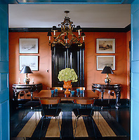 Wallpaper with an orange Wiener Werkstatte pattern covers the walls of a symmetrically furnished dining room
