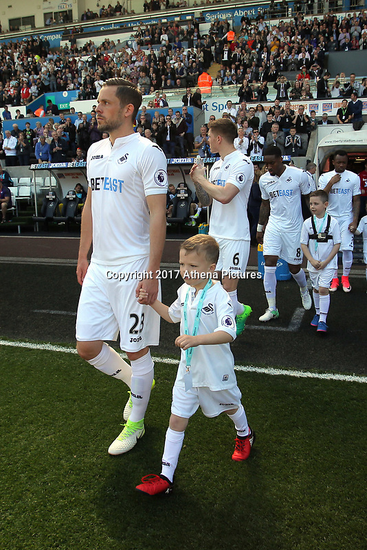 SWANSEA, WALES - APRIL 22: Gylfi Sigurdsson with child mascot during the Premier League match between Swansea City and Stoke City at The Liberty Stadium on April 22, 2017 in Swansea, Wales. (Photo by Athena Pictures/Getty Images)