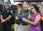 Nevada Highway Patrol Chief Troy Abney and Carson City Sheriff's DARE Officer Lisa Davis watch as Sen. Harry Reid's representative Yolanda Garcia reads a proclamation to Sheriff Ken Furlong during the 11th annual National Night Out hosted by the Carson City Sheriff's Office in Carson City, Nev., on Tuesday, Aug. 6, 2013. <br /> Photo by Cathleen Allison