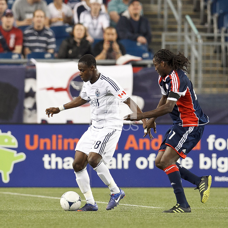 Vancouver Whitecaps FC midfielder Gershon Koffie (28) dribbles as New England Revolution midfielder Shalrie Joseph (21) pressures. In a Major League Soccer (MLS) match, the New England Revolution defeated Vancouver Whitecaps FC, 4-1, at Gillette Stadium on May 12, 2012.