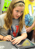 Jessica Urwiler, 11, places a case on her iPad after the Neshaminy Maple Point Middle School students arrived back from the Apple Store Monday August 17, 2015 in Middletown, Pennsylvania. The students will serve as IT ambassadors while helping their classmates and teachers navigate iPad issues this school year. (Photo by William Thomas Cain)