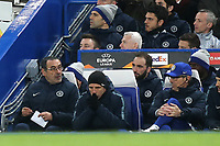 Chelsea Manager, Maurizio Sarri finishes writing some notes while his Assistant, Gianfranco Zola is in deep thought and sitting behind, Gonzola Higuain looks on during Chelsea vs Dynamo Kiev, UEFA Europa League Football at Stamford Bridge on 7th March 2019