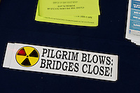 "A bumper sticker reading ""Pilgrim Blows: Bridges Close!"" was given out outside a public hearing regarding Pilgrim Station, a nuclear power plant run by Entergy, at Hotel 1620 in Plymouth, Massachusetts, USA, on Tues., Jan. 31, 2017. An email from the NRC was leaked in December 2016 outlining problems with the ""safety culture"" at the plant and an ""overwhelmed"" staff. Area residents have been calling for the plant to be shut down. The green signs in the audience, reading ""Shut Pilgrim Now,"" are from a group of area residents calling for the plant's closure called Cape Downwinders."