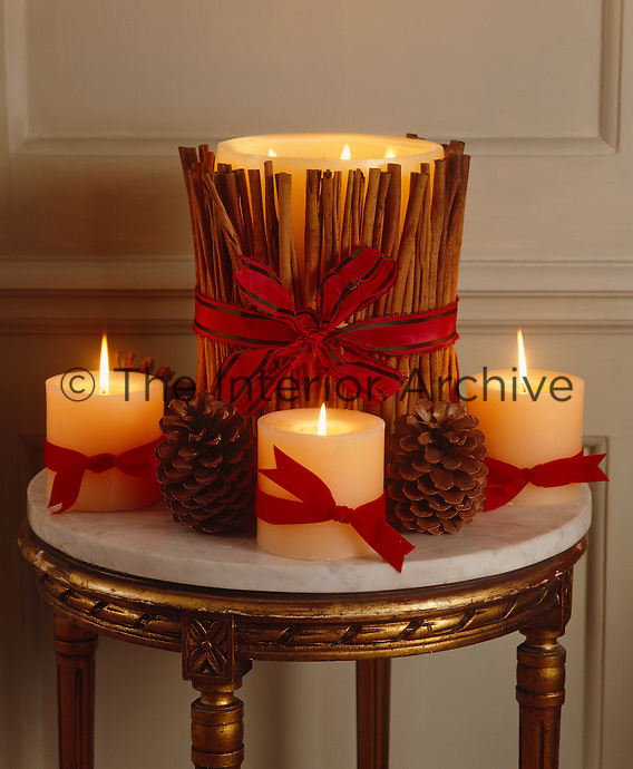 A Christmas candle decoration interspersed with scented pine cones on a small marble-topped table