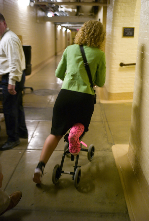 WASHINGTON, DC - July 30: Rep. Debbie Wasserman Schultz, D-Fla., rolls her way, scooter-style, through the U.S. Capitol basement on her way to the House chamber for a series of votes. She sprained her ankle and broke her leg Congressional Women's Softball Game July 15 sliding into second. (Photo by Scott J. Ferrell/Congressional Quarterly)