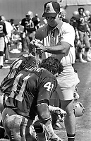 Hot day in San Diego, Raider assistant squeezes water on the neck of Phil Villapiano. (1976 photo/Ron Riesterer)