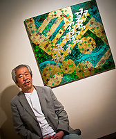 Artist Takashi Satoh seated next to one of his distinctive pieces at his one man Tokyo exhibition.