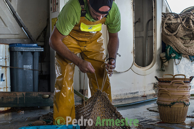"A fisherman checks laces a net on a fishing boat off the coast of Villajoyosa on November 4, 2015. Ecoalf, a Spanish Madrid-based firm founded in 2010, has already launched ""a new generation"" of clothes and accessories made from plastic bottles, old fishing nets and used tires found on land.  © Pedro ARMESTRE"
