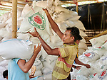 Workers distribute food supplies at an aid distribution by Caritas in the Mainerghona Refugee Camp near Cox's Bazar, Bangladesh, on October 27, 2017. Since August more than 600,000 Rohingya have fled government-sanctioned violence in Myanmar for safety in Bangladesh.